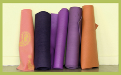 yoga mats rolled and leaning against a wall