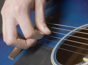 strumming guitar strings