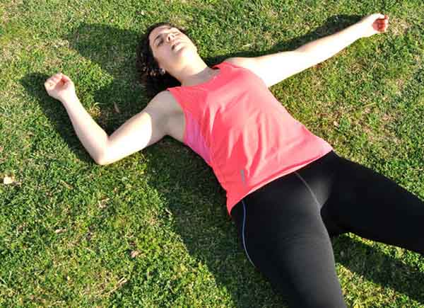 how often can I do yoga-exhausted woman on her back on the grass